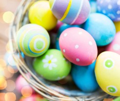 easter, holidays, tradition and object concept - close up of colored easter eggs in basket